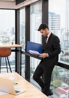 Atrakcyjny biznesmen kaukaski stojący z wyglądającym dokumentem finansowym w biurze