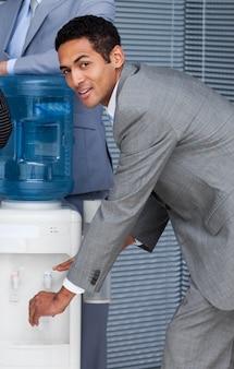 Atrakcyjny biznesmen napełniania kubka z chłodnicy wody