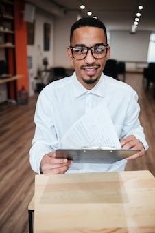 Atrakcyjny biznesmen w okularach siedzący przy stole i patrzący na notatnik