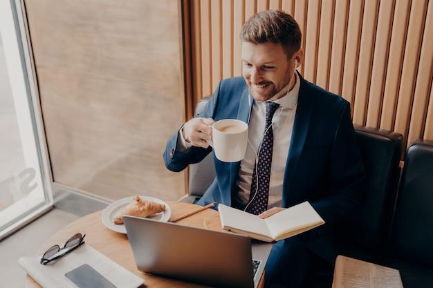 Atrakcyjny biznesmen zdalnie śledzący spotkanie finansowe online z filiżanką latte w ręku w kawiarni i zadowolony z wyników, korzystający z laptopa z wkładkami dousznymi podczas sprawdzania wpisów w skoroszycie