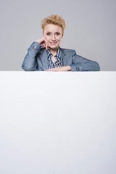 Atrakcyjny bizneswoman i duży plakat