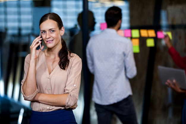 Atrakcyjny bizneswoman ma telefon, podczas gdy koledzy mają spotkanie