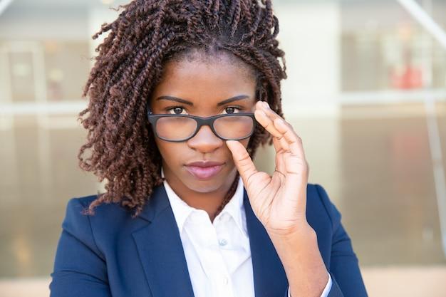 Atrakcyjny bizneswoman przystosowywa okulary