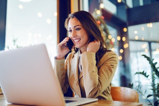 Atrakcyjny bizneswoman w beżowej kurtce siedzi w kawiarni, rozmawia przez telefon i patrzeje laptop.