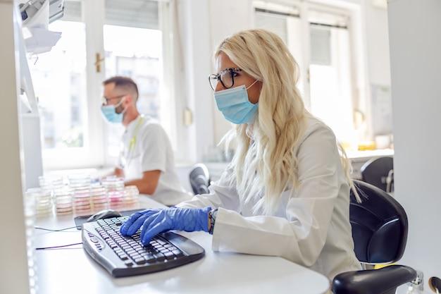 Atrakcyjny blond asystent w laboratorium siedzi w laboratorium i wprowadza dane do komputera. w tle pracuje jej kolega. koncepcja epidemii koronawirusa.