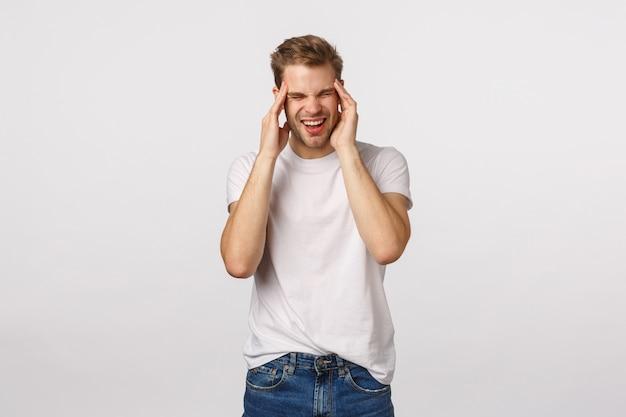 Atrakcyjny blond brodaty mężczyzna w białej koszulce cierpi ból głowy