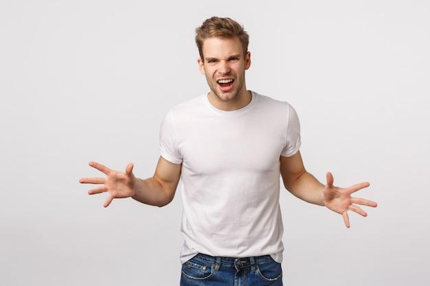 Atrakcyjny blond brodaty mężczyzna w białej koszulce pokazujący siłę
