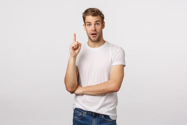 Atrakcyjny blond brodaty mężczyzna w białej koszulce pokazuje palec wskazujący