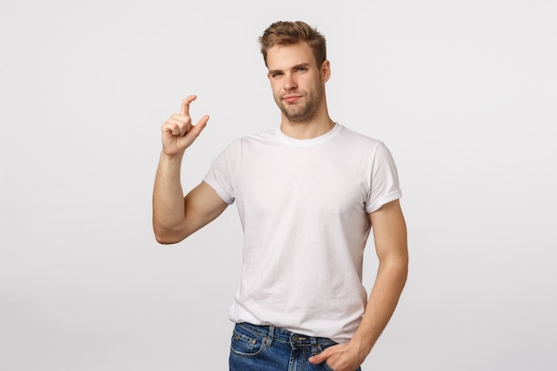 Atrakcyjny blond brodaty mężczyzna w białej koszulce robi drobny gest