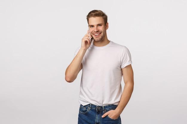 Atrakcyjny blond brodaty mężczyzna w białej koszulce rozmawia przez telefon