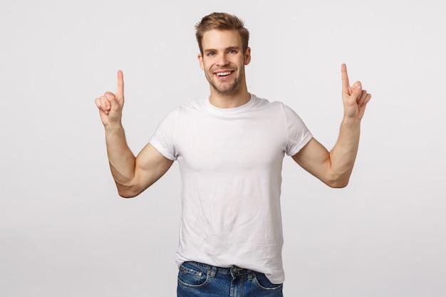 Atrakcyjny blond brodaty mężczyzna w białej koszulce skierowany w górę