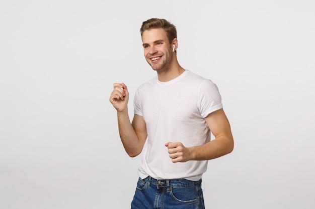 Atrakcyjny blond brodaty mężczyzna w białej koszulce tańczy z bezprzewodowymi słuchawkami