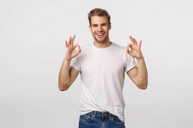 Atrakcyjny blond brodaty mężczyzna w białej koszulce z aprobatą