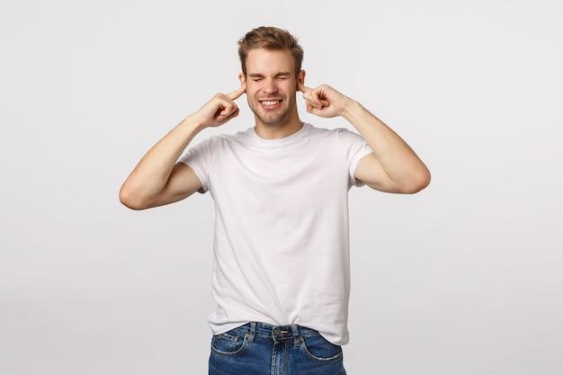Atrakcyjny blond brodaty mężczyzna w białej koszulce z palcami w uszach