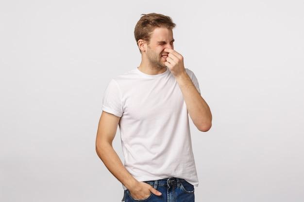 Atrakcyjny blond brodaty mężczyzna w białej koszulce z ręką na nosie
