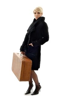 Atrakcyjny blondyn z brązową walizką