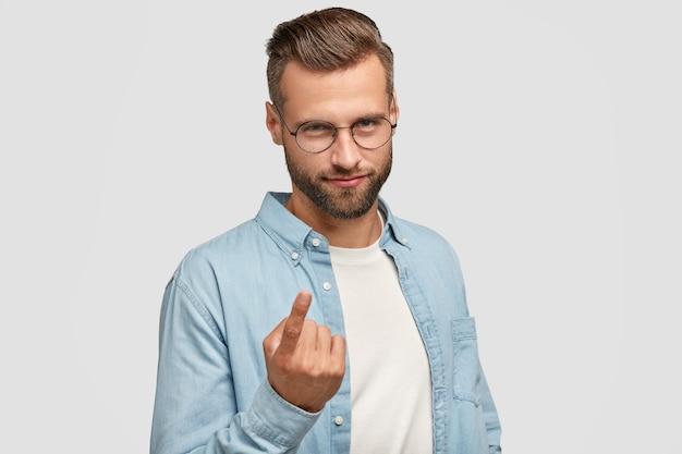 Atrakcyjny brodaty facet pozuje przy białej ścianie