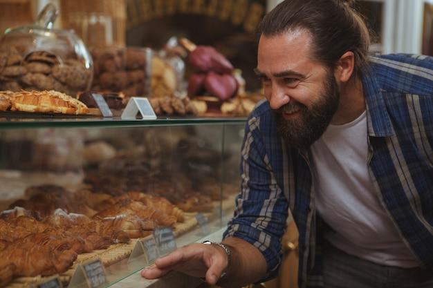 Atrakcyjny brodaty męski klient egzamininuje desery dla sprzedaży na pokazie przy sklep z kawą