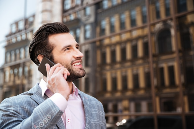 Atrakcyjny brodaty mężczyzna opowiada na telefonie komórkowym w kurtce