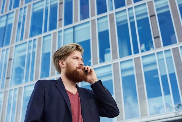 Atrakcyjny brodaty mężczyzna rozmawia przez telefon komórkowy w pobliżu budynku biznesowego z dużymi niebieskimi oknami