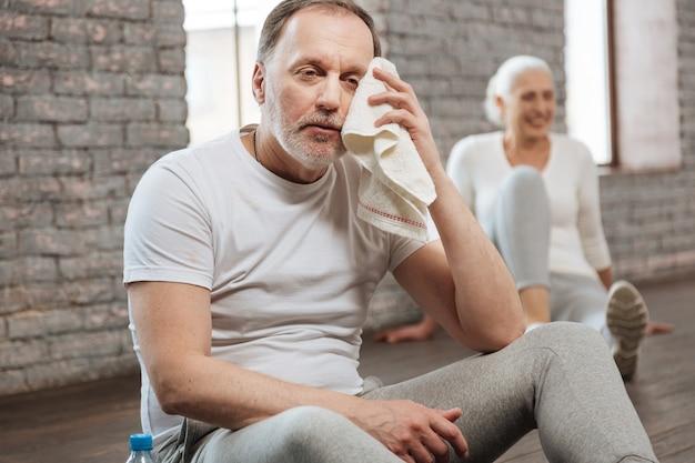 Atrakcyjny brodaty mężczyzna trzymając ręcznik przy oku, kładąc ręce na nogach siedząc na podłodze