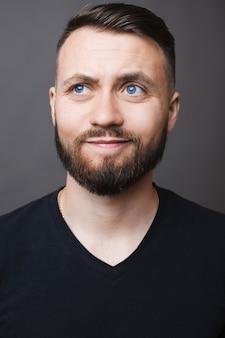 Atrakcyjny brodaty mężczyzna w czarnej koszulce uśmiecha się i patrzy w górę, stojąc na szarym tle i myśląc