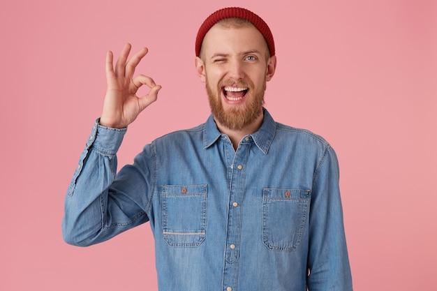 Atrakcyjny brodaty mężczyzna w czerwonej czapce z wymodelowanej dżinsowej koszuli, zadowolony wyraz twarzy, pokazuje znak w porządku, czuje się zadowolony po spotkaniu, odizolowany. wyraz twarzy człowieka, mowa ciała