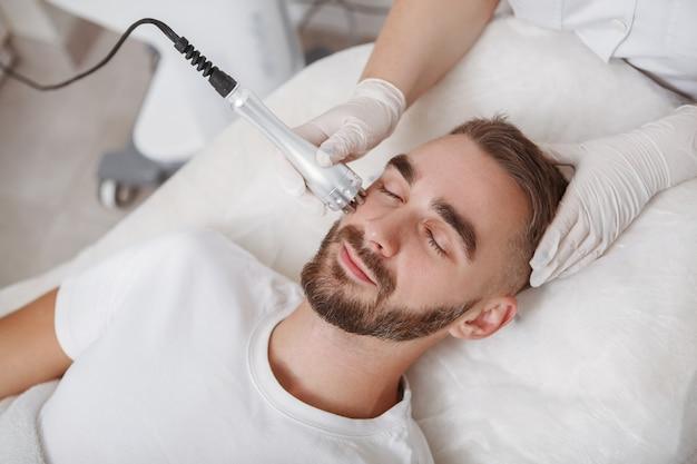 Atrakcyjny brodaty młody człowiek korzystających z zabiegu na twarz sprzęt kosmetologia