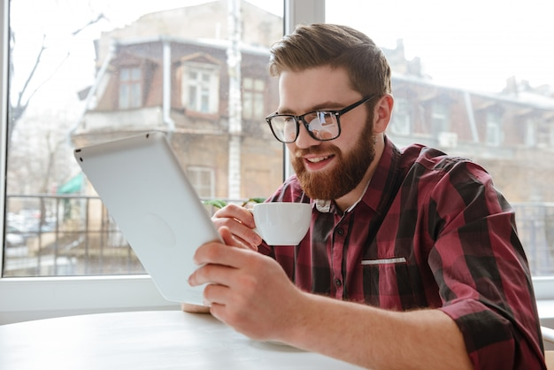 Atrakcyjny brodaty młody człowiek używa pastylka komputer.