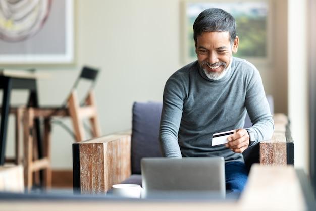Atrakcyjny brodaty modniś azjatykci ojciec lub latynoski stary człowiek używa laptop i kredytowej karty zapłatę