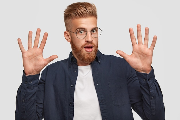 Atrakcyjny, brodaty rudowłosy młody mężczyzna podnosi ręce, pokazuje dłonie, aktywnie gestykuluje, reaguje na coś strasznego, ubrany w luźny strój, pozuje pod białą ścianą.