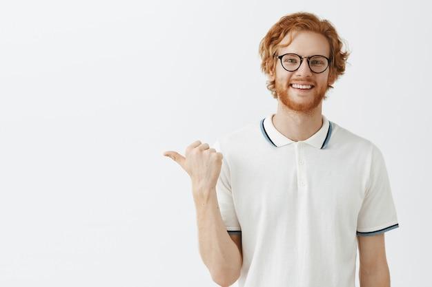 Atrakcyjny brodaty rudy facet pozuje przy białej ścianie w okularach