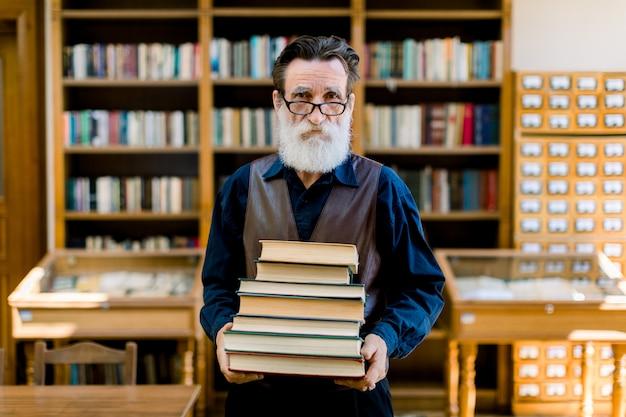 Atrakcyjny brodaty starzec ubrany w koszulę i kamizelkę skórzaną, nauczyciel w szkole średniej lub bibliotekarz, trzymający książki w rękach, stojący w zabytkowym wnętrzu biblioteki. pracownik biblioteki, szczęśliwy dzień książki