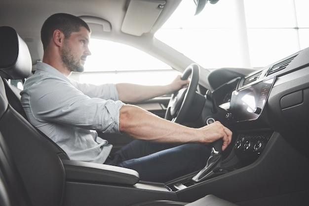 Atrakcyjny brodaty szczęśliwy mężczyzna w dobrym samochodzie.