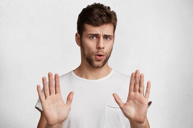 Atrakcyjny brunet pokazuje gest odmowy, nie chce uczestniczyć w spotkaniu, mówi: to nie dla mnie, zostaw mnie w kawałku