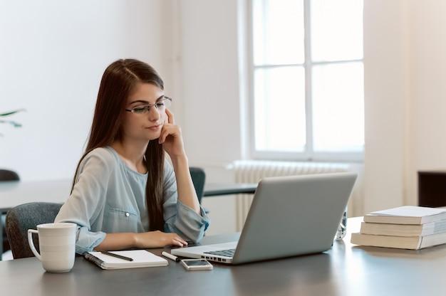 Atrakcyjny brunetka pisarz kobieta siedzi przy stole i pisze na laptopie.