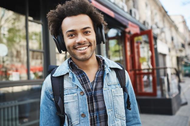 Atrakcyjny ciemnoskóry uśmiechnięty facet z włosiem, słuchający muzyki spacerując po ulicy, będąc w dobrym nastroju