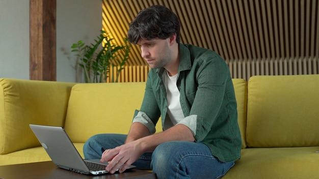 Atrakcyjny czarnowłosy facet przegląda laptopa siedząc w domu na przytulnej żółtej sofie w domu