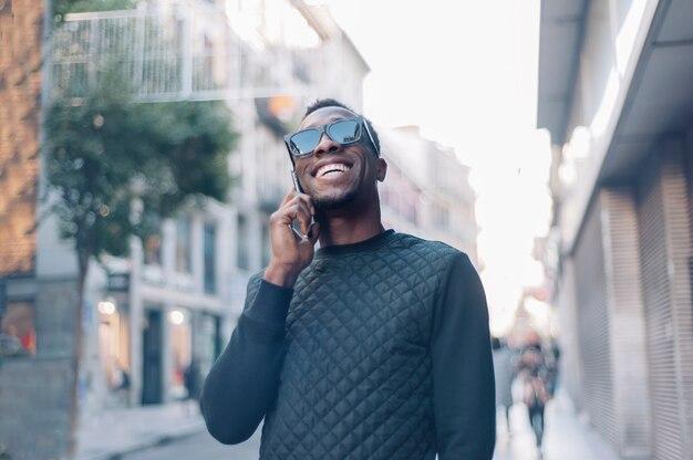 Atrakcyjny czarny człowiek za pomocą telefonu