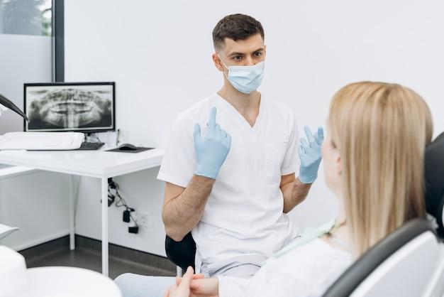 Atrakcyjny dentysta w masce ochronnej komunikuje się z atrakcyjnym pacjentem. dentysta pracuje w gabinecie stomatologicznym