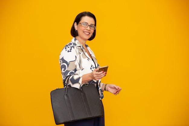 Atrakcyjny dojrzały bizneswoman pracuje z jej telefonem komórkowym