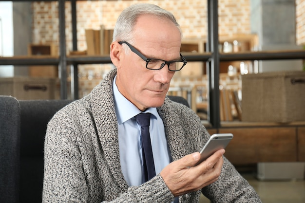 Atrakcyjny dojrzały mężczyzna z telefonem komórkowym w pomieszczeniu