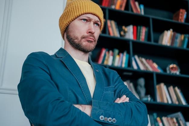 Atrakcyjny dorosły brodaty mężczyzna zły hipster w żółty kapelusz patrzy na aparat i zmarszczone brwi