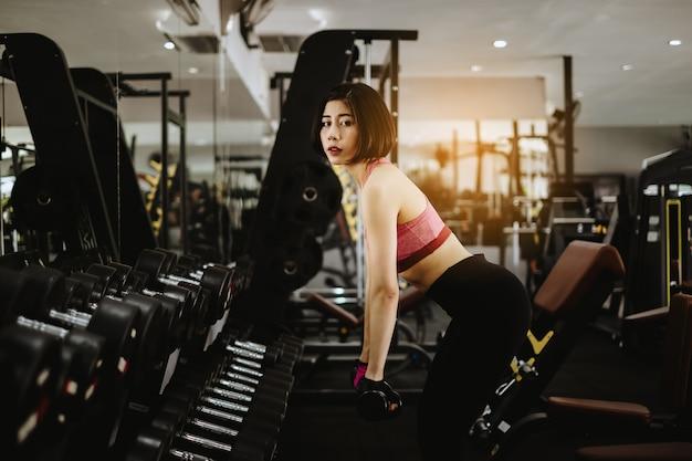 Atrakcyjny dysponowany kobieta trening z dumbbell w gym sprawności fizycznej