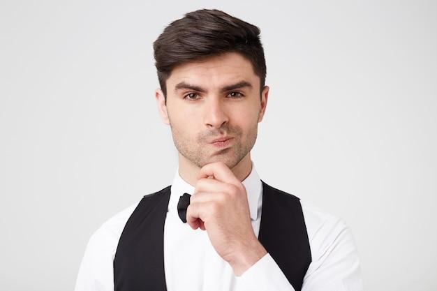 Atrakcyjny dżentelmen stoi trzymając dłoń na brodzie, jeden kącik ust jest lekko wciśnięty, patrzy w zamyśleniu