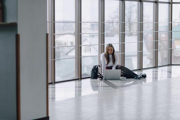Atrakcyjny dziewczyny obsiadanie na podłoga z laptopem i rzeczami w lotniskowym terminal lub biurze. atmosfera podróży lub alternatywna atmosfera pracy.