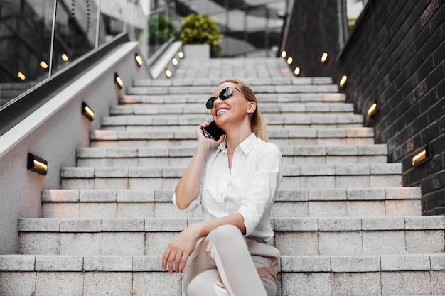 Atrakcyjny efektowny uśmiechnięty pozytywny blond modna kobieta siedzi na schodach na zewnątrz i za pomocą smartfona.