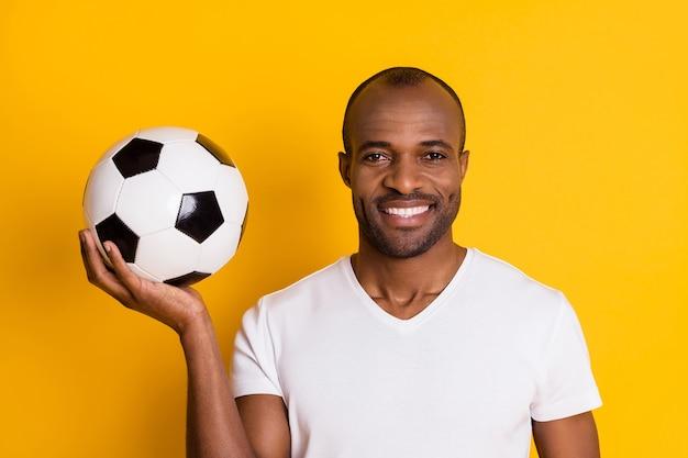 Atrakcyjny facet mężczyzna trzyma skórzaną piłkę futbolową ząb uśmiechnięty