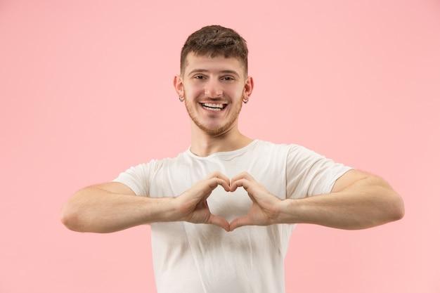 Atrakcyjny facet robi symbol w kształcie serca palcami.