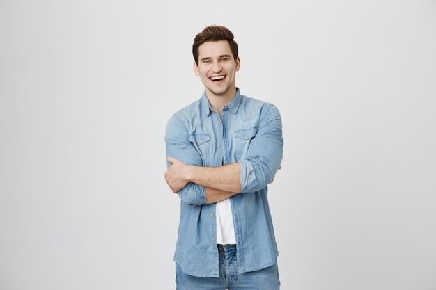 Atrakcyjny facet roześmiany zabawy, uśmiechnięty szczęśliwy